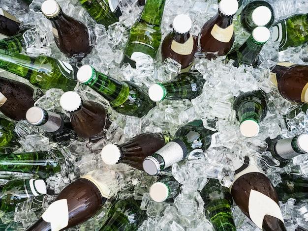 Eiswürfel und bunte flaschen mit kaltem bier Premium Fotos