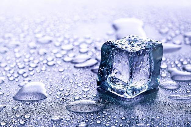 Eiswürfel und wasser schmelzen auf kühlem hintergrund. eisblöcke mit kalten getränken oder getränken. Premium Fotos