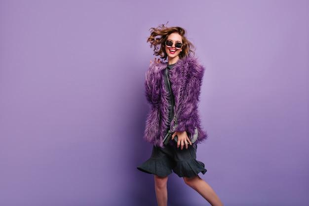 Ekstatische frau im kleid und in der flauschigen jacke, die mit lachen tanzen Kostenlose Fotos