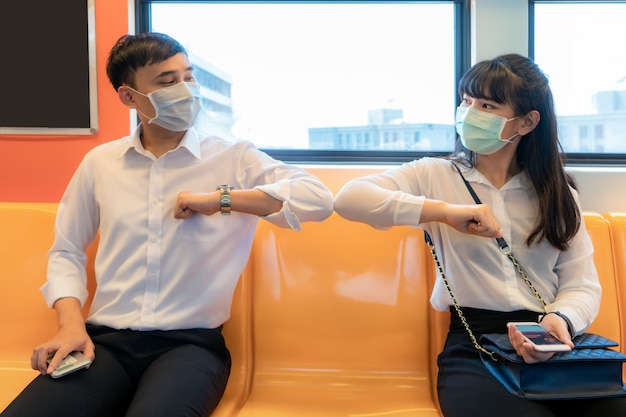 Elbow bump ist eine neue neuartige begrüßung, um die ausbreitung des coronavirus zu verhindern. zwei asiatische geschäftsfreunde treffen sich in der u-bahn. Premium Fotos