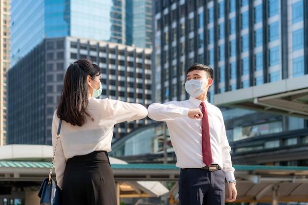 Elbow bump ist eine neue neuartige begrüßung, um die ausbreitung des coronavirus zu verhindern. zwei asiatische geschäftsfreunde treffen sich vor dem bürogebäude. Premium Fotos