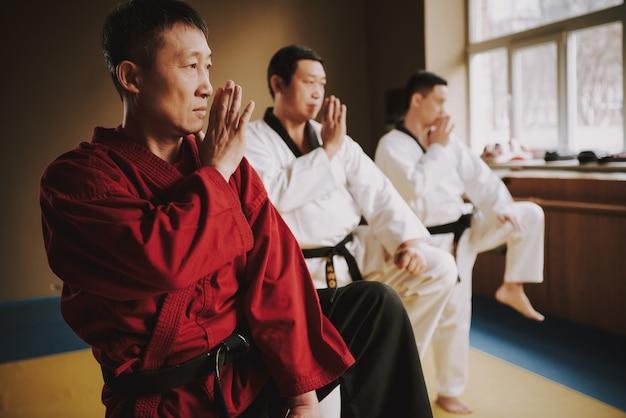Elder sensei in rot und zwei kampfsportstudenten trainieren Premium Fotos