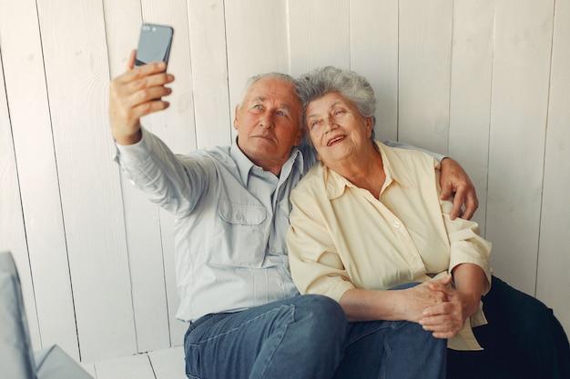 Elegante alte paare, die zu hause sitzen und ein telefon verwenden Kostenlose Fotos