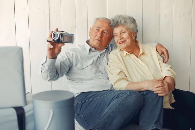 Elegante alte paare, die zu hause sitzen und eine kamera verwenden Kostenlose Fotos