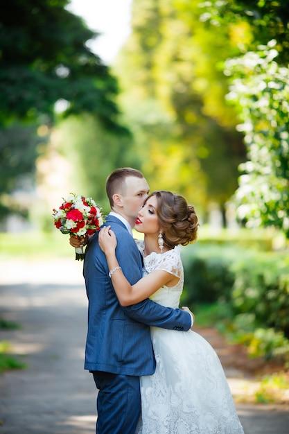 Elegante braut und bräutigam, die zusammen draußen an