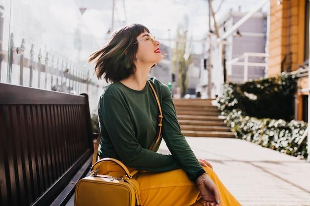 Elegante europäische frau mit dem geraden kurzen haar, das auf bank sitzt. außenporträt des erstaunlichen weißen mädchens trägt grünen pullover im frühlingstag. Kostenlose Fotos