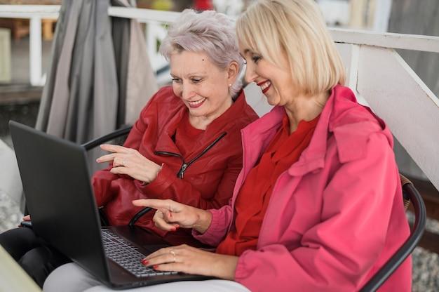 Elegante fällige frauen, die einen laptop verwenden Kostenlose Fotos