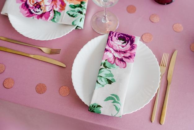 Elegante festliche tischdekoration in rosatönen mit floralen textilservietten, goldener gabel und messer, konfetti. hochzeit, geburtstag, babyparty, mädchenpartydekoration. Premium Fotos