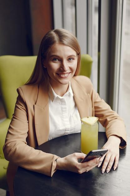 Elegante frau, die am tisch mit cocktail und telefon sitzt Kostenlose Fotos