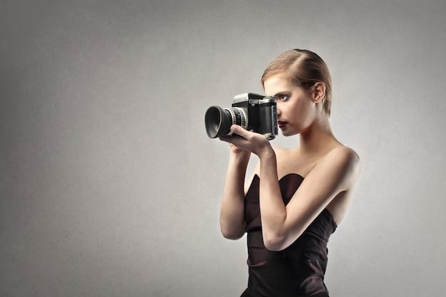 Elegante frau, die eine kamera anhält Premium Fotos