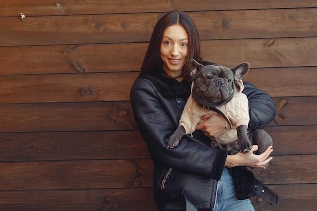 Elegante frau in einer schwarzen jacke mit schwarzer bulldogge Kostenlose Fotos