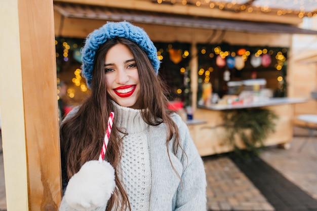 Elegante frau mit hellem make-up, das mit lutscher nahe weihnachtsmarkt am kalten tag aufwirft. erfreutes europäisches weibliches modell trägt wollmantel, der neujahrsbonbons hält und lacht. Kostenlose Fotos