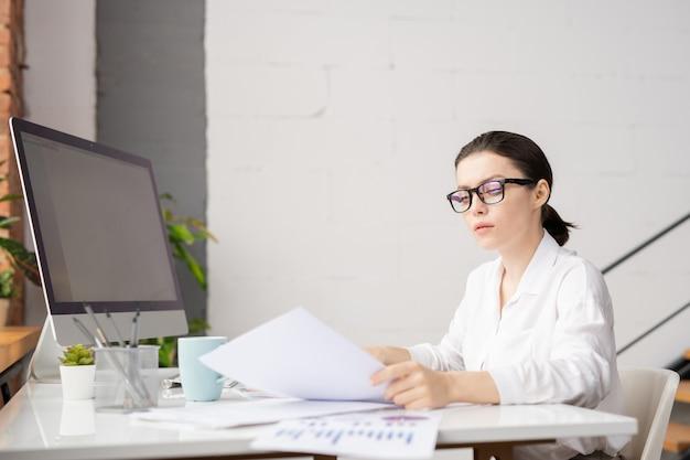 Elegante geschäftsfrau der jungen brünette in den brillen und im weißen hemd, die papiere durch schreibtisch im büro lesen Premium Fotos