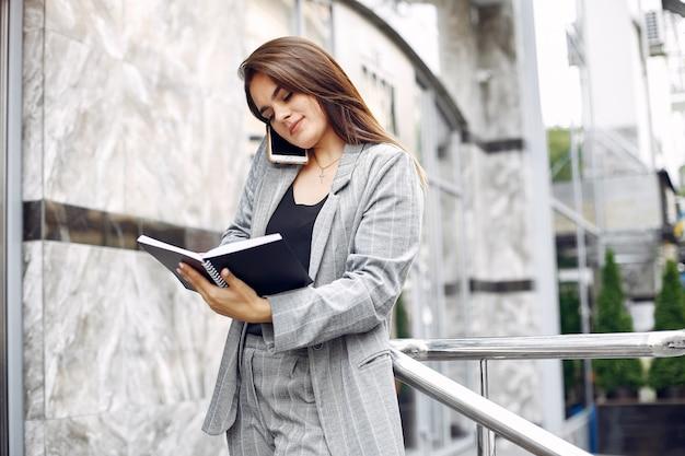 Elegante geschäftsfrau, die in einer stadt arbeitet und das notizbuch benutzt Kostenlose Fotos