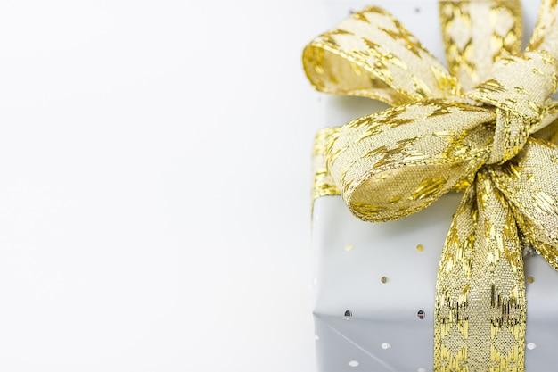 Elegante geschenkbox in grauem silberpapier mit polka dots golden ribbon. Premium Fotos
