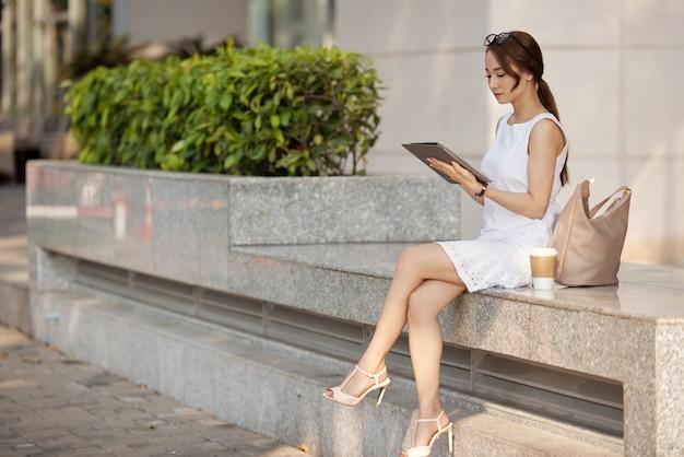 Elegante junge asiatin, die auf steinbank sitzt und tablette verwendet Kostenlose Fotos
