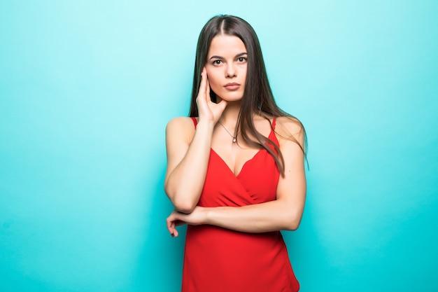 Elegante junge attraktive frau, die rotes sommerkleid mit den händen am kinn lokalisiert über pastellblauer wand trägt. Kostenlose Fotos