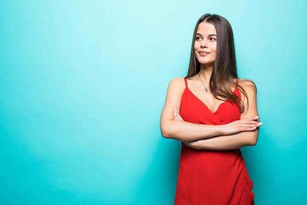 Elegante junge attraktive frau, die rotes sommerkleid mit gekreuzten händen über pastellblauer wand isoliert trägt. Kostenlose Fotos
