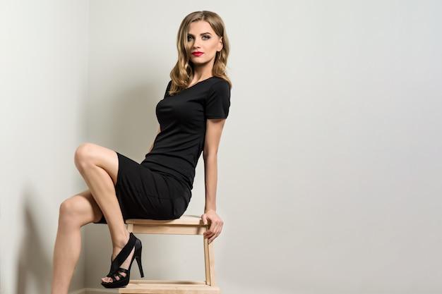 Elegante junge frau blond im schwarzen kleid Premium Fotos