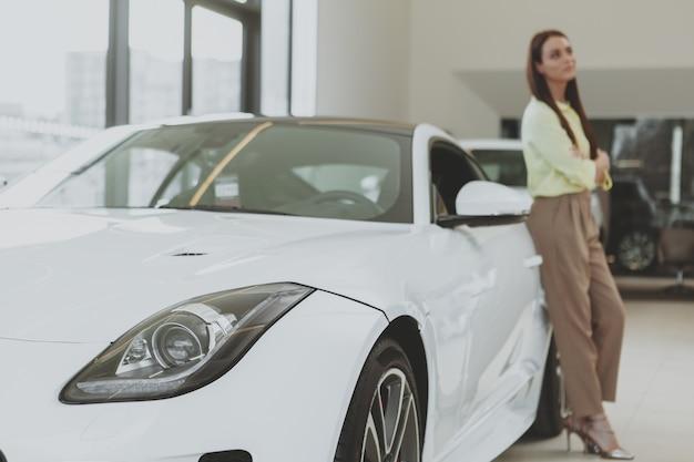 Elegante junge frau, die neues auto an der verkaufsstelle kauft Premium Fotos