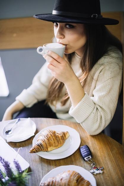 Elegante junge frau im hut mit becher des getränks bei tisch im café Kostenlose Fotos
