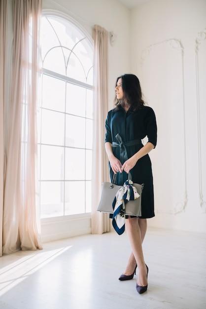 Elegante junge frau im kleid mit handtasche im raum Kostenlose Fotos