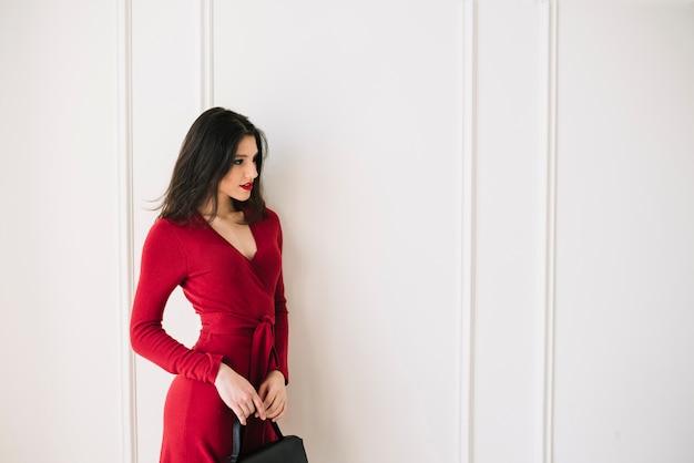 Elegante junge frau im roten kleid mit handtasche im raum Kostenlose Fotos