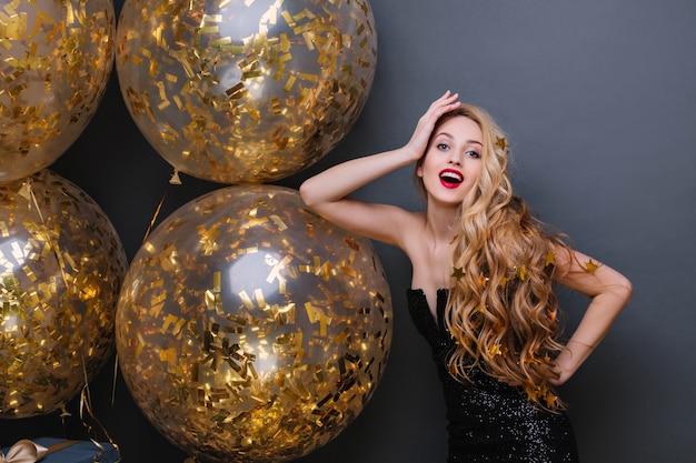 Elegante junge frau mit langen blonden haaren, die in der selbstbewussten pose auf neujahrsparty stehen. innenporträt des charmanten geburtstagskindes, das mit funkelnden luftballons aufwirft. Kostenlose Fotos