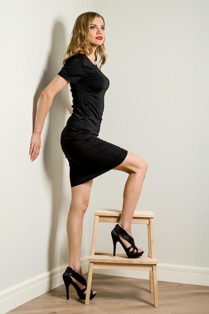 Elegante junge geschäftsfrau blond im schwarzen kleid Premium Fotos