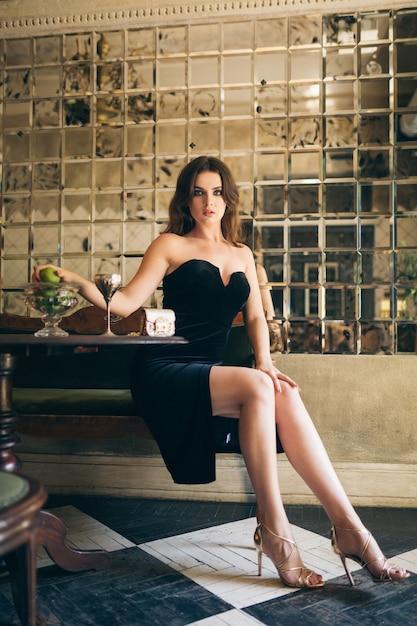 Elegante schöne frau sitzt im vintage-café im schwarzen samtkleid, abendkleid, reiche stilvolle dame, eleganter modetrend, sexy verführerischer blick, attraktive dünne figur mit langen beinen in den absätzen Kostenlose Fotos