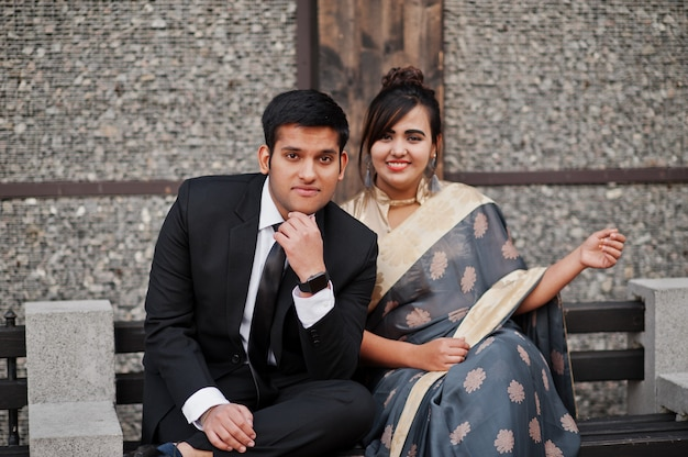 Elegante und moderne indische freundpaare der frau im saree und des mannes in der klage, die auf bank sitzt. Premium Fotos
