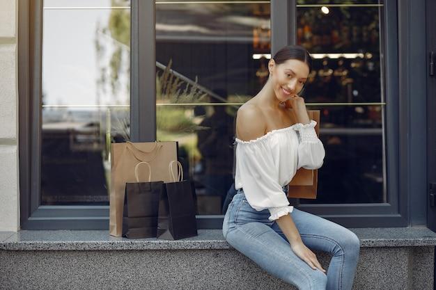 Elegante und stilvolle mädchen auf der straße mit einkaufstüten Kostenlose Fotos