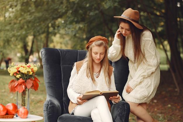 Elegante und stilvolle mädchen, die auf einem stuhl in einem park sitzen Kostenlose Fotos