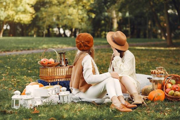 Elegante und stilvolle mädchen, die in einem park sitzen Kostenlose Fotos