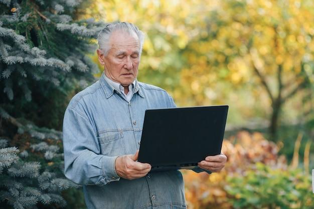 Eleganter alter mann, der auf grauem hintergrund steht und einen laptop benutzt Kostenlose Fotos