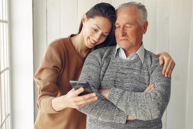 Eleganter alter mann, der zu hause mit seiner enkelin steht Kostenlose Fotos