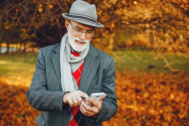 Eleganter alter mann in einem sonnigen herbstpark Kostenlose Fotos