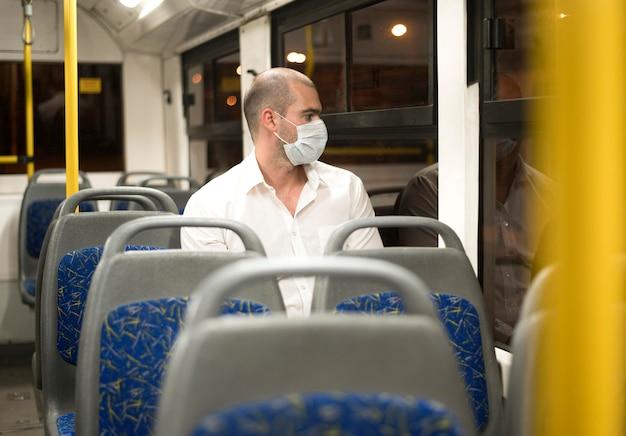 Eleganter erwachsener männlicher reitbus mit medizinischer maske Kostenlose Fotos