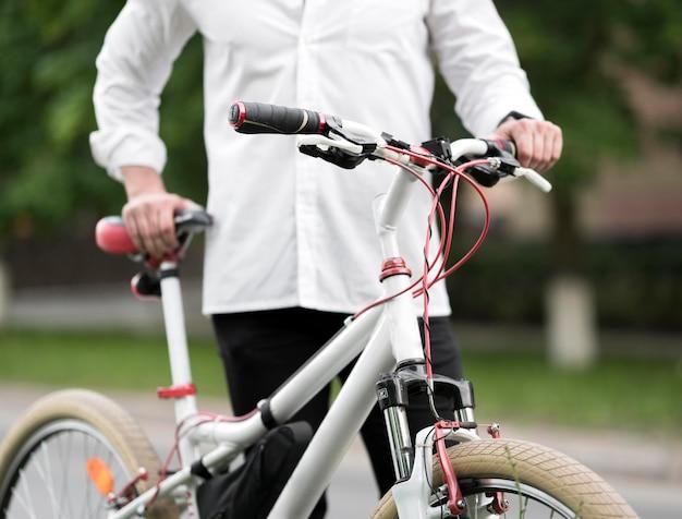 Eleganter erwachsener mann, der modernes fahrrad hält Kostenlose Fotos