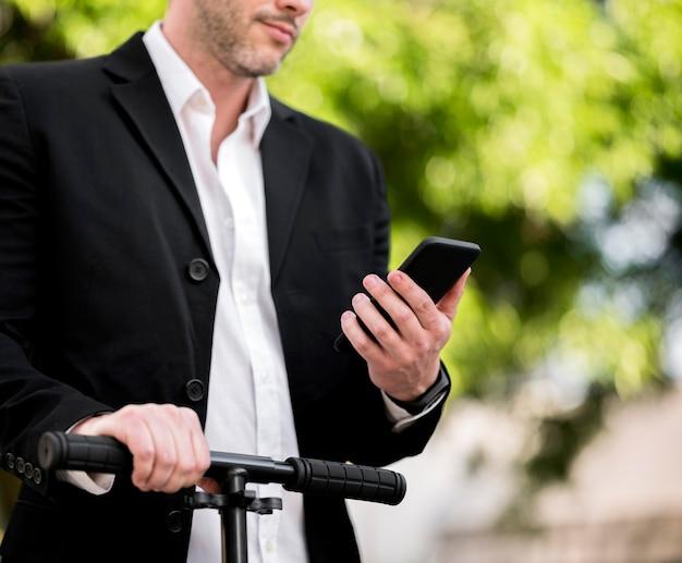 Eleganter geschäftsmann, der roller draußen reitet Kostenlose Fotos