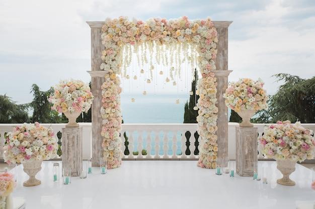 Eleganter hochzeitsbogen mit frischen blumen, vasen auf ozean und blauem himmel. Premium Fotos