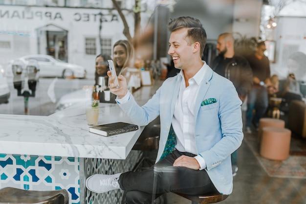 Eleganter junge, der in einer bar plaudert auf dem mobile sitzt Kostenlose Fotos