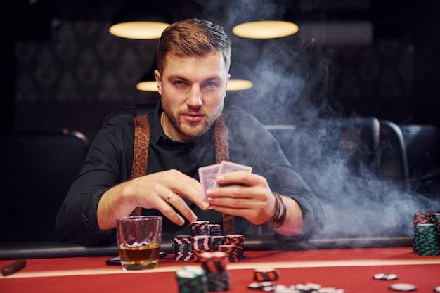 Eleganter junger mann sitzt im kasino mit rauche darin und spielt pokerspiel Premium Fotos