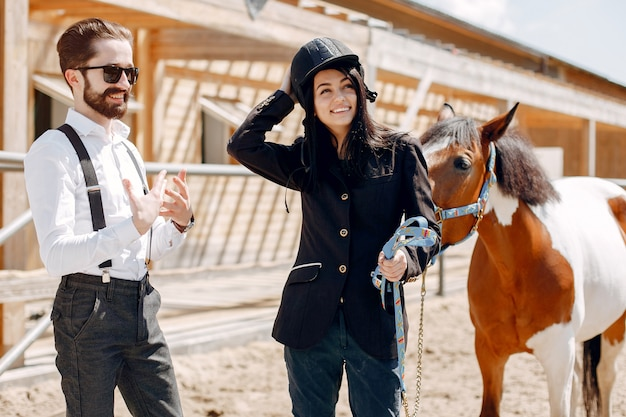 Eleganter mann, der nahe bei pferd in einer ranch mit mädchen steht Kostenlose Fotos