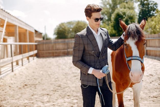 Eleganter mann, der nahe bei pferd in einer ranch steht Kostenlose Fotos