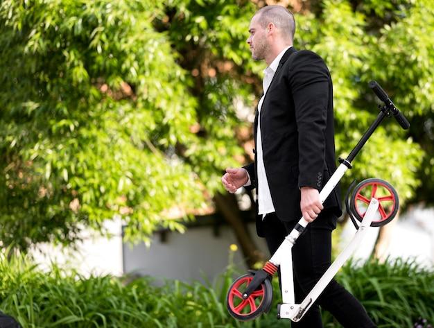 Eleganter mann, der roller im freien trägt Kostenlose Fotos