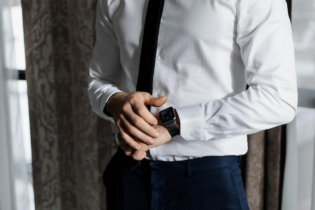 Eleganter mann, gekleidet in ein weißes hemd und eine krawatte mit einer intelligenten uhr Kostenlose Fotos