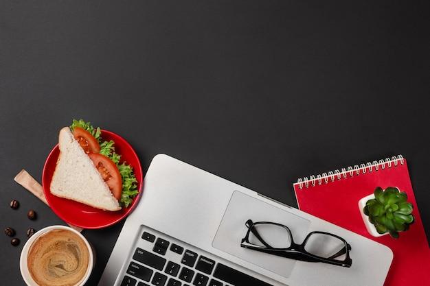 Eleganter schwarzer bürodesktop mit laptop, tasse kaffee und einem sandwich für das mittagessen in der draufsicht Premium Fotos