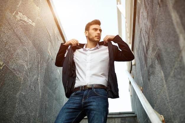 Eleganter und moderner geschäftsmann in der jacke, die auf dem klassischen architekturgebäude der treppe steht. Premium Fotos