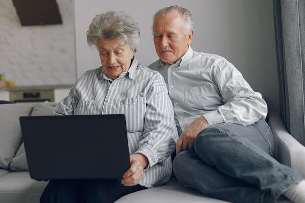 Elegantes altes ehepaar, das zu hause sitzt und einen laptop benutzt Kostenlose Fotos